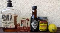 Zutaten für den Old Fashioned: Bourbon Whiskey, Demerara-Würfelzucker, Aromatic Bitters, Maraschino-Kirschen und eine Zitrone.