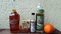 Zutaten für den Sazerac: Rye Whiskey, Demerara-Würfelzucker, Peychaud's Bitters, Absinth und eine Orange.