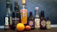 Zutaten für den Hooker Cocktail: Bourbon, Scotch, Averna, Belgisches Bier, Zuckersirup, Cococlate Bitters, Boker's Bitters, Orangensaft und ein Ei.
